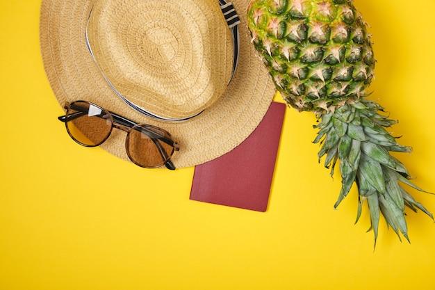 Ananas, hoed, zonnebril en internationaal paspoort op gele achtergrond tropen vakantie concept kopie ruimte