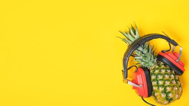 Ananas in rode retro koptelefoon op gele achtergrond met kopie ruimte