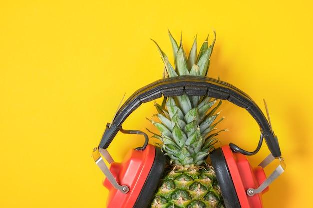 Ananas in rode retro koptelefoon op gele achtergrond