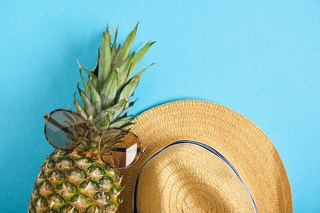 Ananas in zonnebril en strohoed op blauwe achtergrond