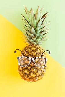 Ananas in zonnebril op veelkleurige achtergrond