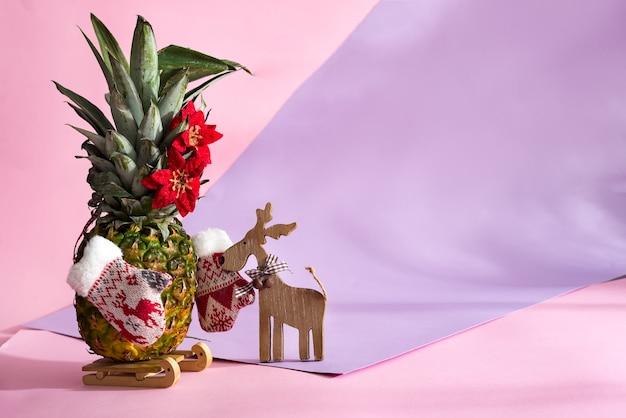 Ananas kerstboom met winter wanten en kerst bloemen op groene bladeren
