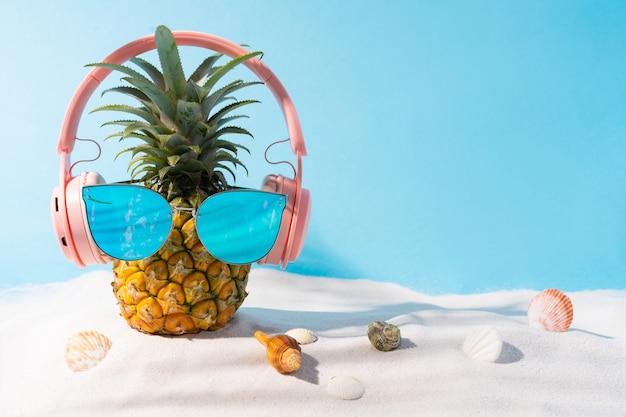 Ananas met koptelefoon en zonnebril op het zand