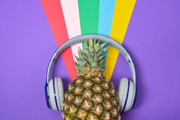 Ananas met koptelefoon op een kleurrijke achtergrond met kopieerruimte, bovenaanzicht