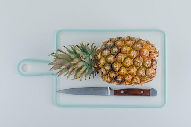 Ananas met mes op witte snijplank