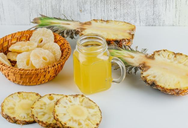 Ananas met sap en gekonfijte ringen op rieten mand