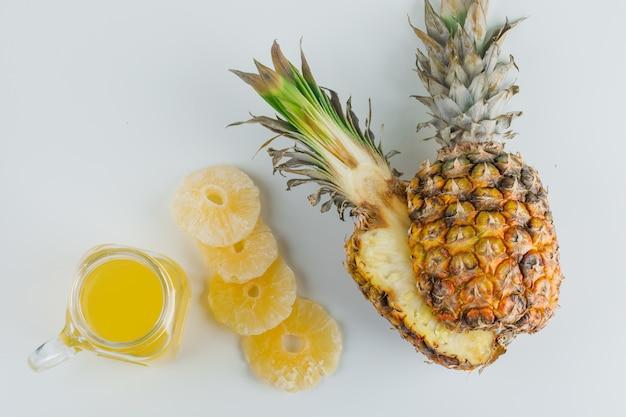 Ananas met sap en gekonfijte ringen op wit oppervlak