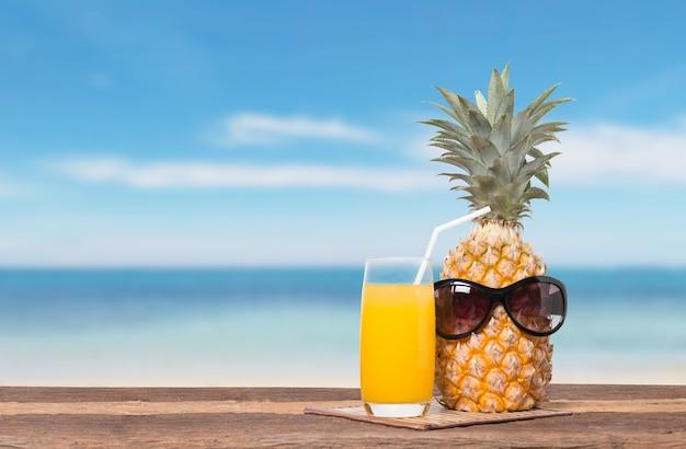 Ananas met sap op het strand tafel en de blauwe lucht voor de zomer concept