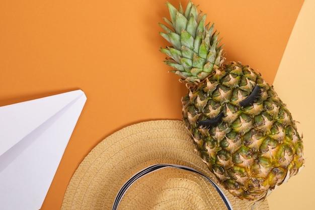 Ananas met wimpers aan, een strohoed en papieren vliegtuigje op oranje achtergrond