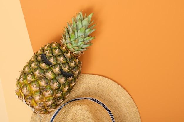 Ananas met wimpers en een strohoed op oranje achtergrond