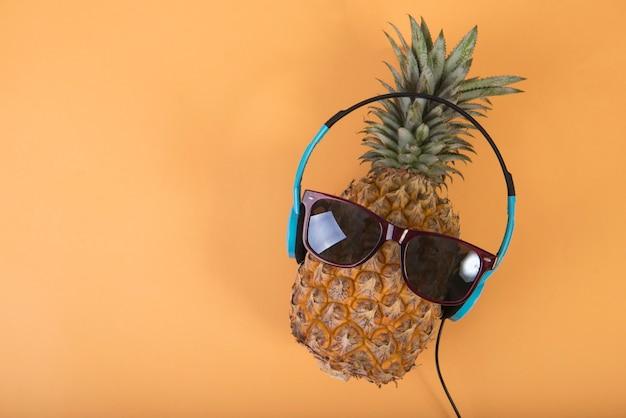 Ananas met zonnebril en hoofdtelefoon op oranje achtergrond. fruit zomer concept.