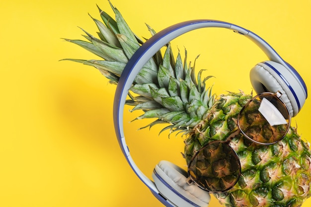 Ananas met zonnebril en koptelefoon op gele achtergrond