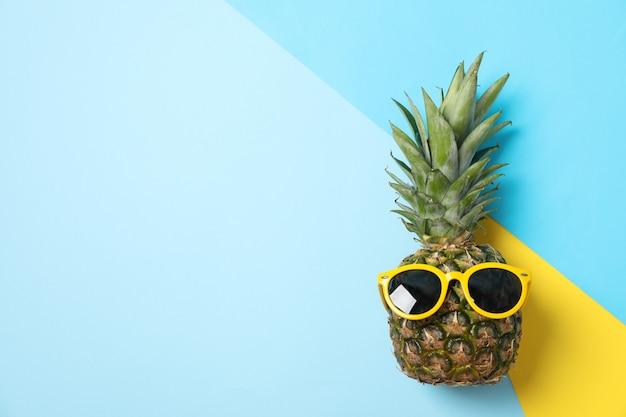 Ananas met zonnebril op drie toon achtergrond, ruimte voor tekst