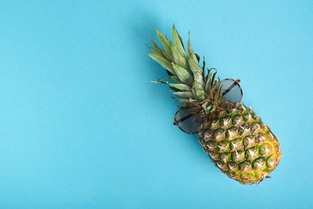 Ananas met zonnebril op een blauwe achtergrond met kopieerruimte