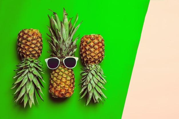 Ananas op gekleurd papier met een bril