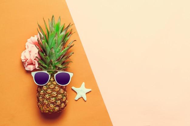 Ananas op gekleurd papier met glazen