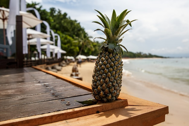 Ananas op het houten bureau op het zomerstrand.