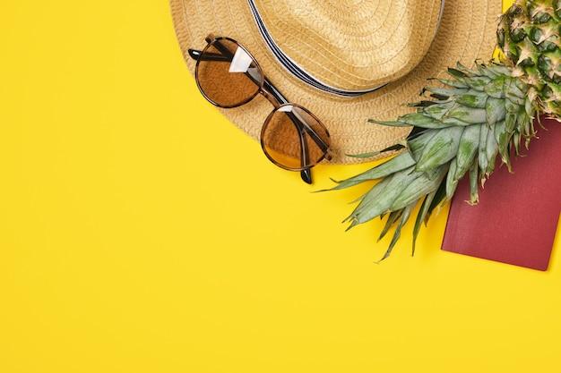 Ananas, strohoed, zonnebril en leeg paspoort op gele achtergrond met exemplaarruimte copy