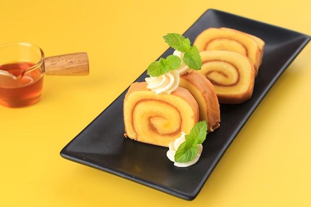 Ananasbroodjescake of bolu gulung nanas, dunne cake gerold met ananasjam met kaasglazuur erop. ruimte kopiëren op gele achtergrond