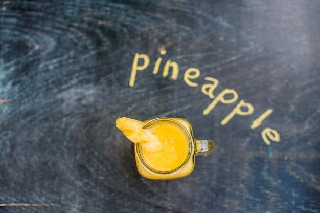 Ananascocktail met een plakje op houten achtergrond en inschrijving in krijt. tropisch concept