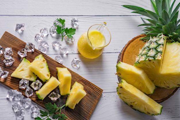 Ananascocktail of sap met ijs en ananassen op een donkere achtergrond