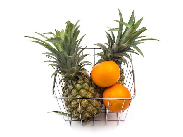 Ananassen en sinaasappelen in de mand op een witte achtergrond