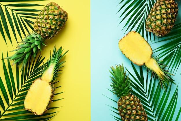 Ananassen, palmbladen op pastelkleur kleurrijke gele en turkooise achtergrond met exemplaarruimte.