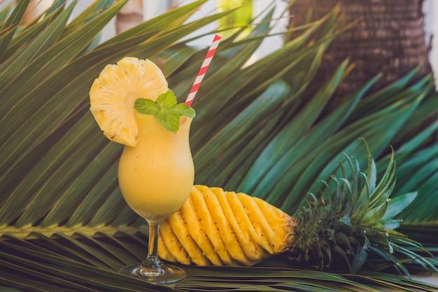 Ananassmoothies en ananasfruit tegen de achtergrond van een palmblad