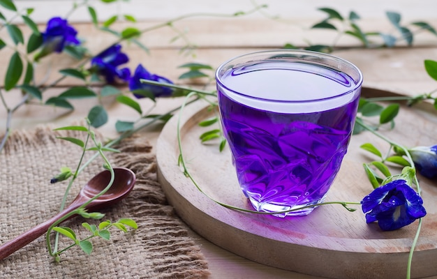Anchan bloemsap of blauwe erwtenbloem kruidenthee, vlindererwt in glazen beker met houten lepel op houten tafel