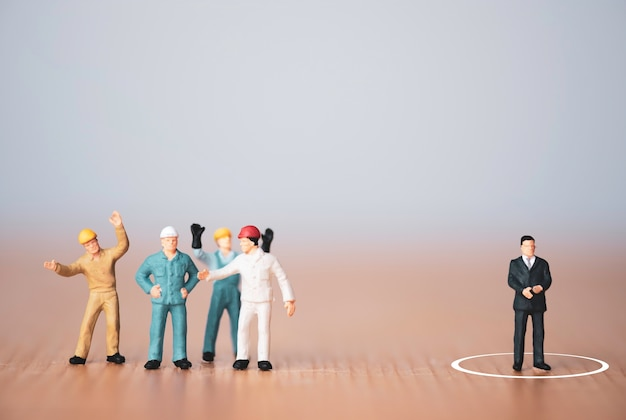 Ander denk- en leiderschapsconcept, miniatuurfiguurmanager gescheiden van stafmedewerkers.