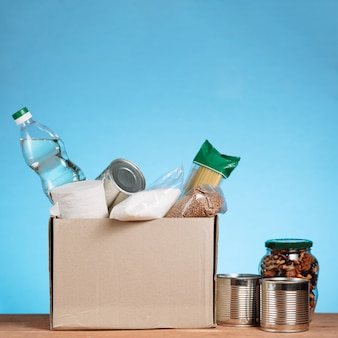 Ander eten in een vrijwilligersbox. doneer box, donatie en liefdadigheidsconcept. donatiebox met voedsel op blauwe achtergrond. vierkant beeld
