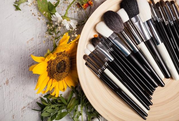 Ander type make-upborstels op een bord naast wilde bloemen op houten achtergrond