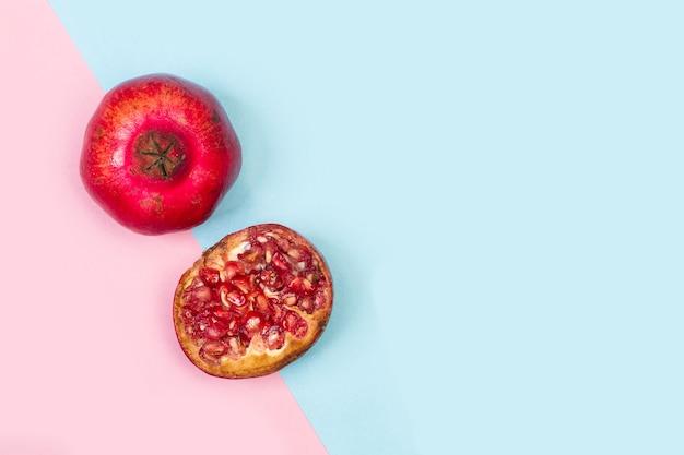 Anderhalve granaatappel op een roze en lichtblauwe achtergrond