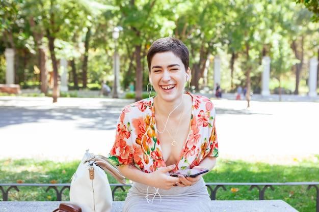 Androgyne vrouw lachen met behulp van technologie