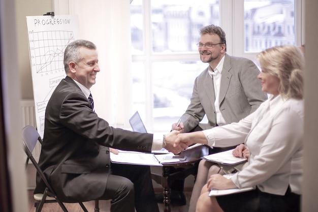 Andshake van een zakenman en zakenvrouw tijdens een vergadering op kantoor