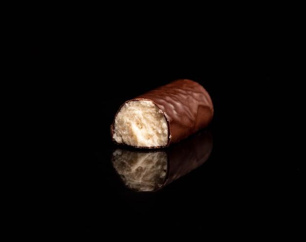 Ð¡andy met kokos die chocolade invult die op houten lijst op zwart wordt geïsoleerd