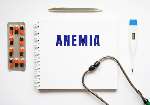 Anemia-tekst geschreven in een notitieboekje dat op een bureau en een stethoscoop ligt