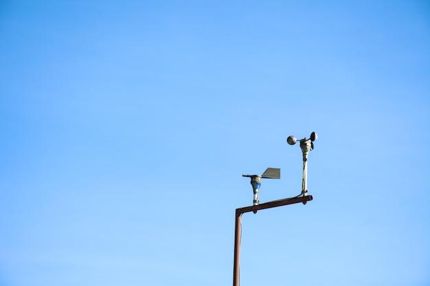 Anemometer in meteorologisch weerstation met blauwe hemelachtergrond.