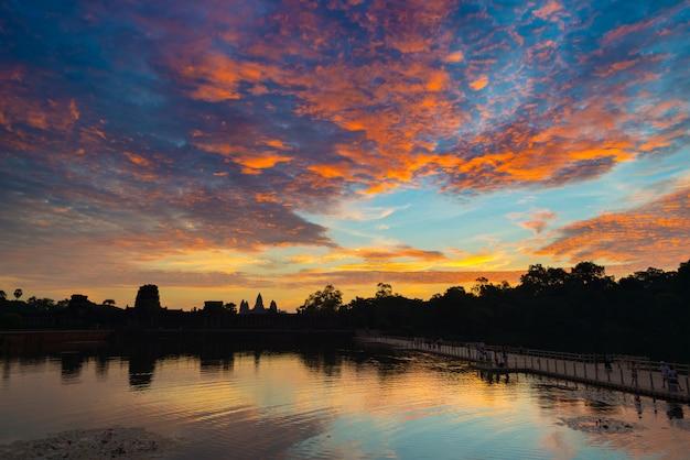 Angkor wat dramatische hemel bij het silhouetbezinning van de dag belangrijkste hoofdvoorgevel over watervijver