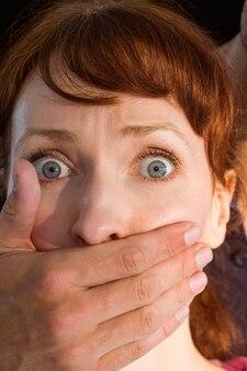 Angst aangejaagde vrouw met overdekte mond