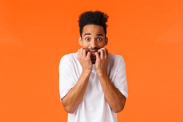 Angst, horrorfilms, emoties concept. bang en onzeker, jonge timide hipster afro-amerikaanse man, vingernagels bijten, camera angstig staren, bang dat iemand weet, oranje achtergrond