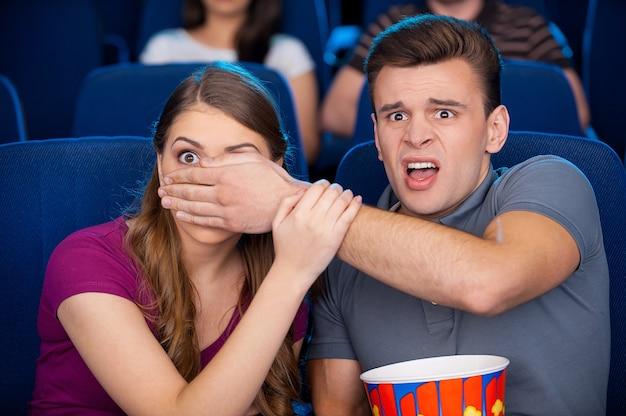 Angstaanjagend moment. geschokt jong stel kijken samen naar een enge film terwijl ze in de bioscoop zitten