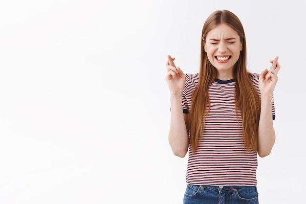 Angstig hoopvol jong blond kaukasisch meisje in gestreept t-shirt bidden, tanden op elkaar klemmen nerveus ogen dicht en vingers gekruist veel geluk, anticiperend op iets belangrijks, nerveus wachtend