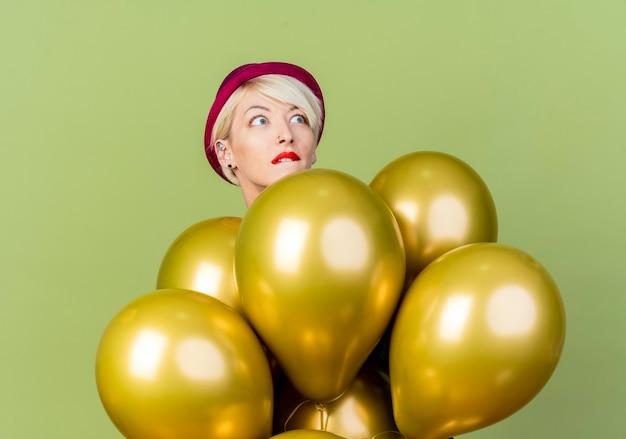 Angstig jong blond feestmeisje die partijhoed dragen die zich achter ballons bevinden die kant bijten lip bekijken die op olijfgroene achtergrond wordt geïsoleerd