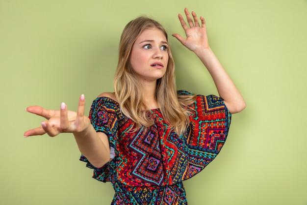 Angstig jong blond slavisch meisje dat met opgeheven handen staat en naar de zijkant kijkt