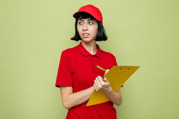 Angstig jong kaukasisch bezorgmeisje met klembord en pen kijkend naar de zijkant?