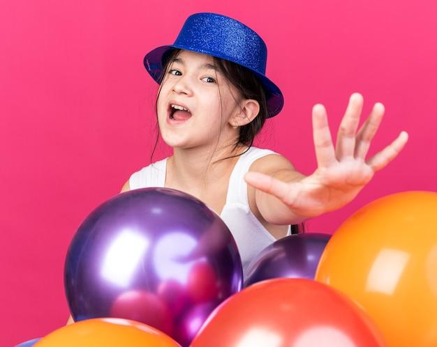 Angstig jong kaukasisch meisje dat een blauwe feestmuts draagt die zich met heliumballons bevindt en hand uitrekt die op roze muur met exemplaarruimte wordt geïsoleerd