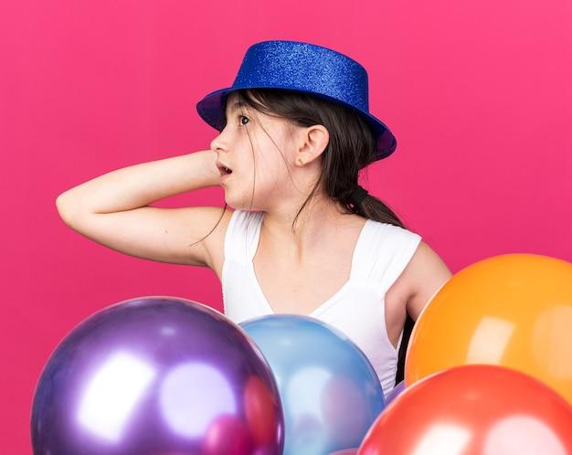 Angstig jong kaukasisch meisje met blauwe feestmuts staan met helium ballonnen hand op het hoofd zetten en kijken naar kant geïsoleerd op roze muur met kopie ruimte