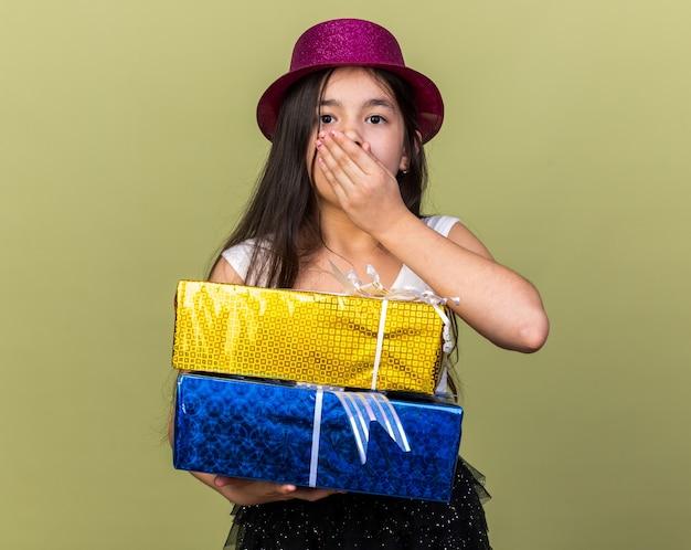 Angstig jong kaukasisch meisje met paarse feestmuts hand op de mond zetten en geschenkdozen geïsoleerd op olijfgroene muur met kopie ruimte te houden