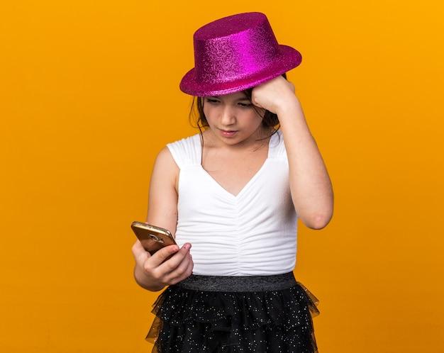Angstig jong kaukasisch meisje met paarse feestmuts vuist op voorhoofd houden en kijken naar telefoon geïsoleerd op oranje muur met kopie ruimte